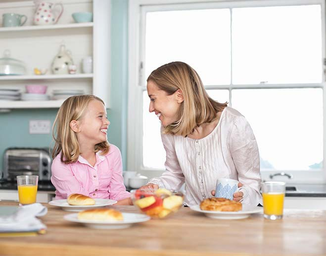 happy mom and daughter eating breakfast