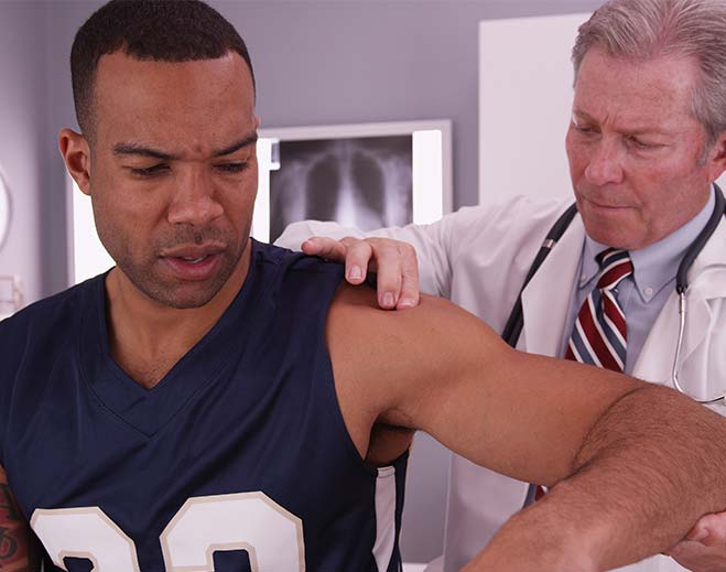 man being treated by sports medicine doctor